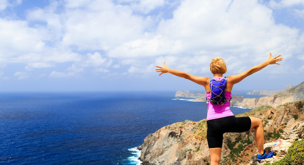 A woman enjoying a hike overlooking the ocean without any allergies.